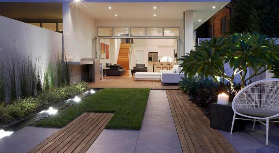 На фото дворик таунхауса з екзотичними рослинами і ліхтариками.