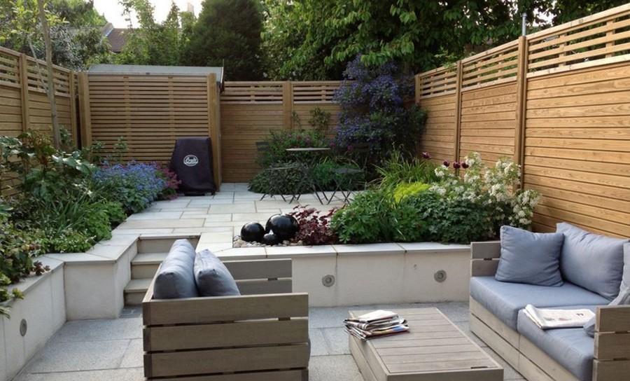 На фото дворик таунхауса,в якому стоять диван,крісло і столик,а вздовж паркану ростуть квіти.
