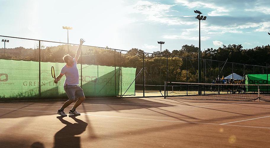 На фото чоловік грає в теніс.