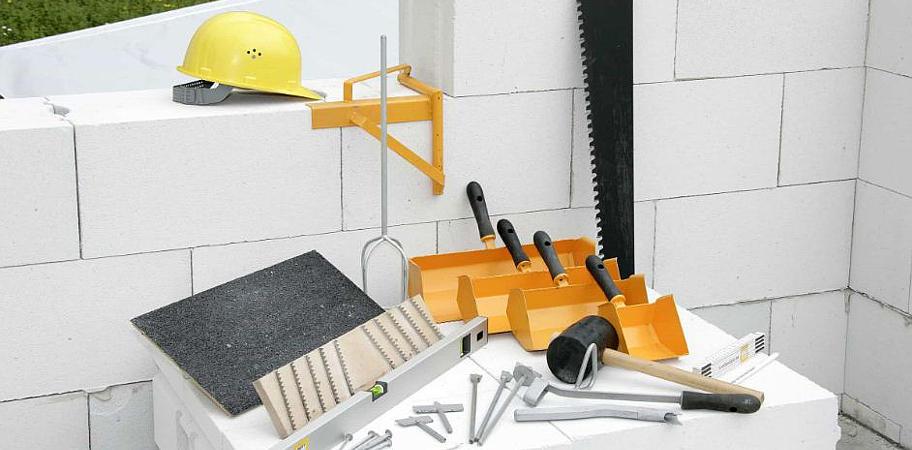 на фото инструменты строителя  таунхаусов . Савхаус будуємо якісно