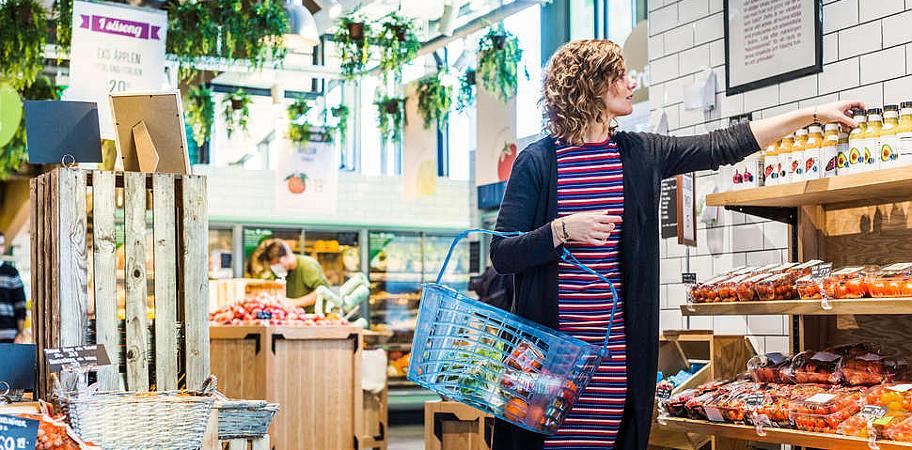 на фото женщина которая на рынке выбирает овощи
