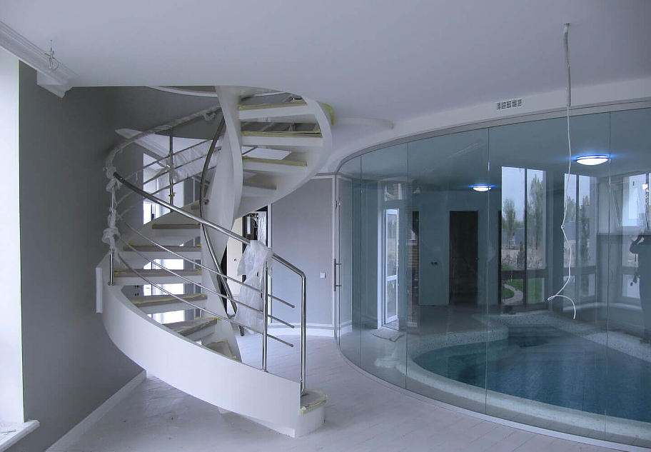 На фото гвинтові сходи,білого кольору,з металевою обробкою,виготовленої в сучасному стилі.