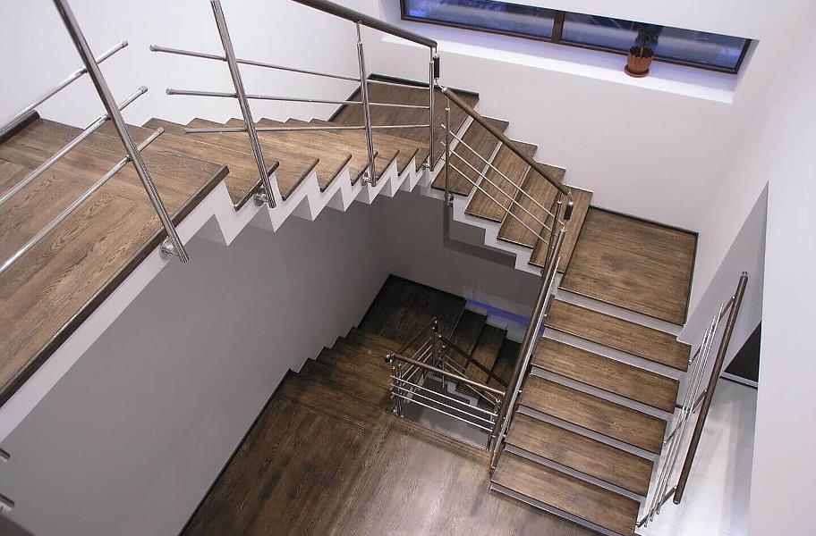 На фото сходи з подвійним каркасом,покриті ламінатом та огороджені металевими перилами.