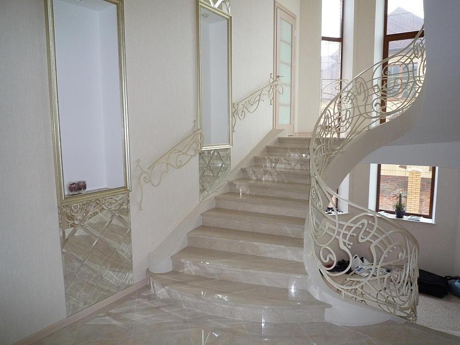 На фото мармурові сходи світлого кольору з білими кованими перилами.